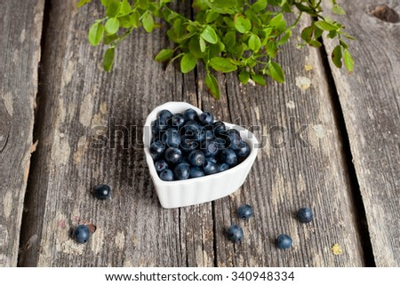 Heart shaped bowl of blueberries on wooden table, horizontal, close up - stock photo