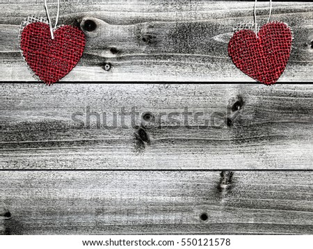 Heart Shaped Burlap on Wood Background - Photograph of heart shaped pieces of red and tan burlap hanging at the top of a wood background with a grunge filter on the image.  Blank space for text.