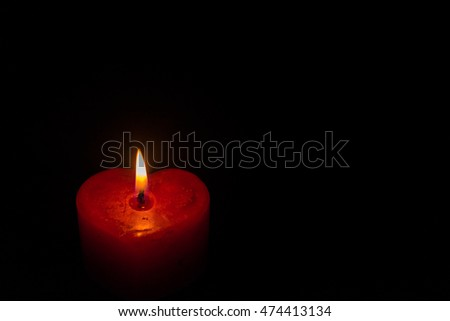 heart shaped burning candle against dark background