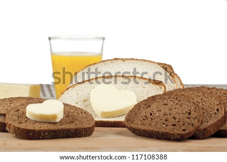 Heart shaped butter and bread slices arranged creatively over the dining table - stock photo