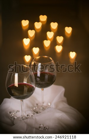 heart shaped candle lights with wine glasses - stock photo