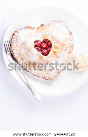 Heart shaped cherry pie with vanilla ice cream on white background