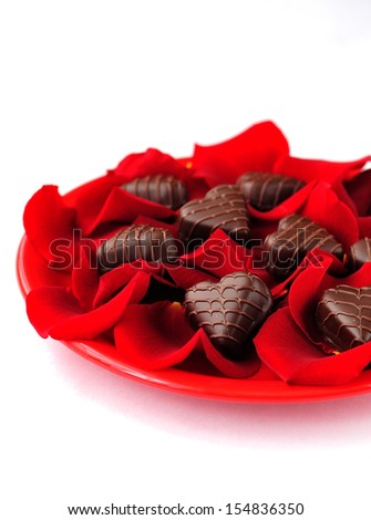 Heart-shaped chocolate candies with rose petals, St. Valentine - stock photo