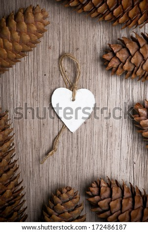 Heart shaped Christmas decoration and spruce cones on wooden table. Merry Christmas.  handmade ornament in center of photo. Empty white heart for your own text or message. greeting card.