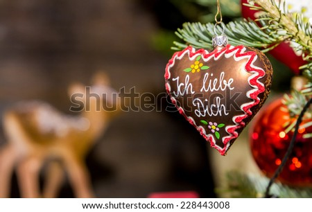 "Heart-shaped Christmas ornament at a Christmas Market, depicting a gingerbread heart with the words ""I love you"" in German language - stock photo"