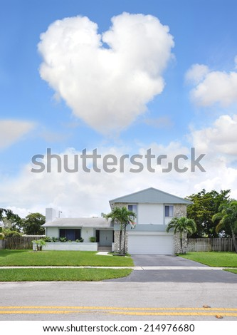 Heart shaped Cloud over Suburban Back Split Style home in residential neighborhood USA Blue Sky Clouds - stock photo
