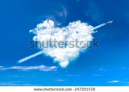 Heart shaped clouds in blue sky with plane