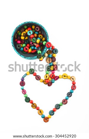 Heart shaped colorful handmade wooden round beads necklace partly taken out of jewelry box isolated on white