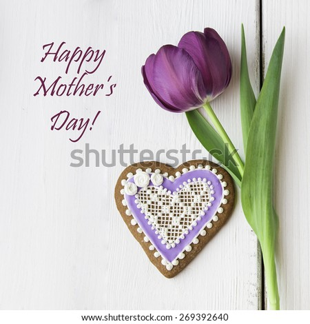 Heart shaped cookie and tulip flower for Mother's day. - stock photo