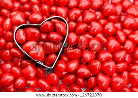 Heart shaped cookie cutter surrounded by cinnamon candy hearts - stock photo