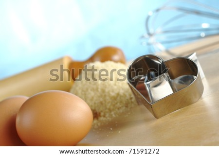 Heart shaped cookie cutter with baking ingredients and utensils such as eggs, brown sugar, rolling pin and a beater (Selective Focus, Focus on the front of the cookie cutter)