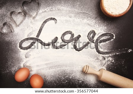 Heart - shaped cookie cutters, flour and word Love, made with it, and other stuff for baking cookies, lying on black table. - stock photo