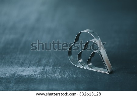 heart shaped cookie cutters on dark colored table. very shallow depth of field