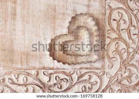 Heart shaped cookie cutters on distressed wood with decorative carved border.   - stock photo