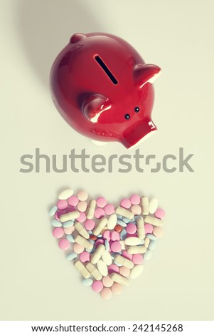 Heart shaped drugs and red piggy bank. Investment health care concept - stock photo
