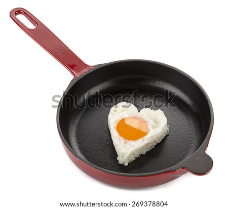 Heart shaped egg on cast iron cookware isolated on white background. - stock photo