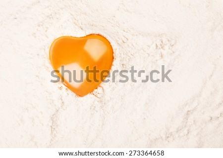 Heart-shaped egg yolk on flour on black background - stock photo
