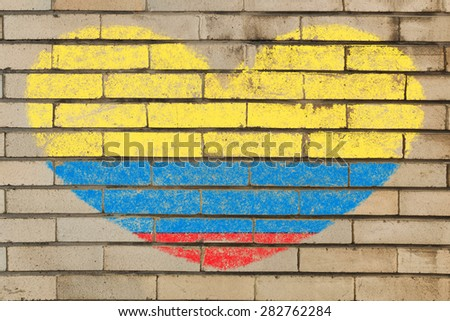 heart shaped flag in colors of Colombia on brick wall