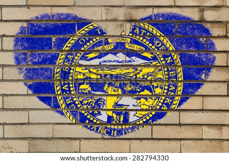 heart shaped flag in colors of nebraska on brick wall - stock photo
