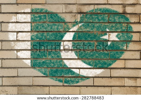 heart shaped flag in colors of Pakistan on brick wall