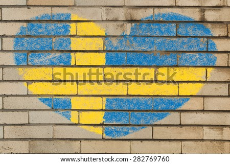heart shaped flag in colors of Sweden on brick wall - stock photo