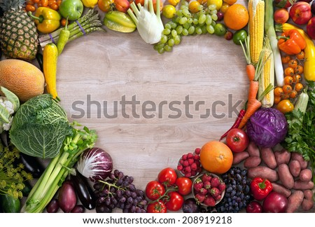 Heart shaped food / food photography of heart made from different fruits and vegetables on wooden table  - stock photo