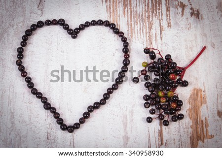 Heart shaped fresh elderberry and bunch of fresh berry on old rustic wooden background, symbol of love, healthy nutrition and alternative medicine - stock photo