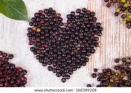 Heart shaped fresh elderberry and green leaf on old rustic wooden background, symbol of love, healthy nutrition and alternative medicine - stock photo