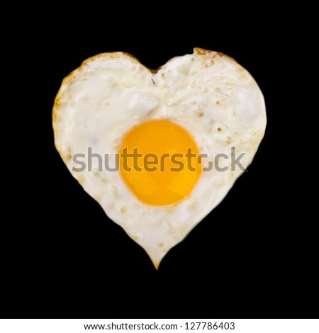 Heart shaped fried egg on frying pan