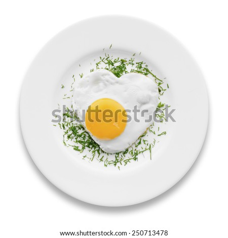 Heart-shaped fried egg with herbs on a white plate isolated - stock photo