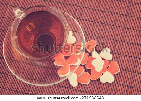 Heart shaped fruit candy and cup of tea on red bamboo background - stock photo