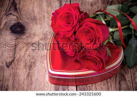 Heart-shaped gift box and bouquet of  red roses for valentine's day on wooden background. - stock photo