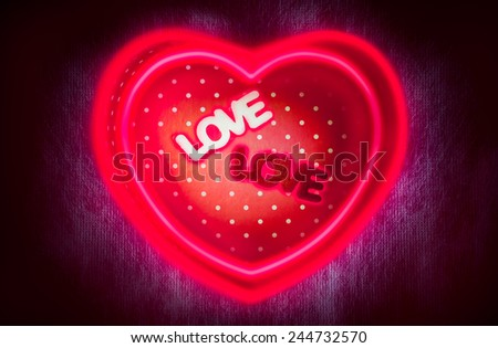 """Heart-shaped gift box and two text """"LOVE"""" middle box with double magic heart-shape neon or fluorescent light lines on dark background low key lighting picture style for a Valentine's day, love concept - stock photo"""
