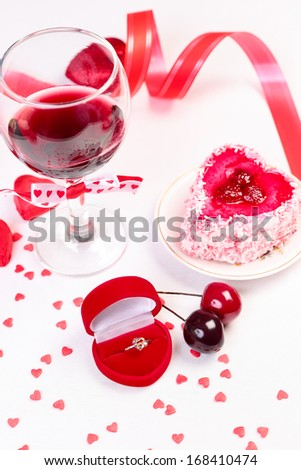 Heart shaped gift box with ring, glass of wine and valentine day decorations - stock photo