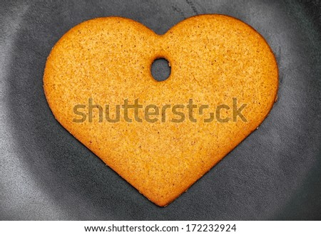 Heart shaped gingerbread cookie on the black plate, close up, top view - stock photo