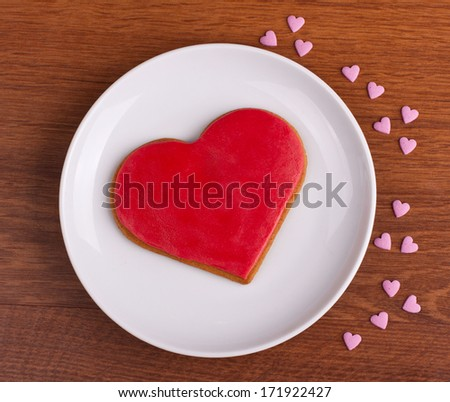 Heart shaped gingerbread cookie on white plate shot from above