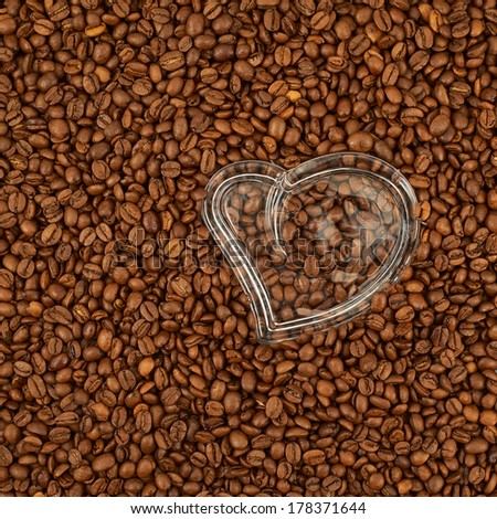 Heart shaped glass figure over the surface covered with coffee beans - stock photo