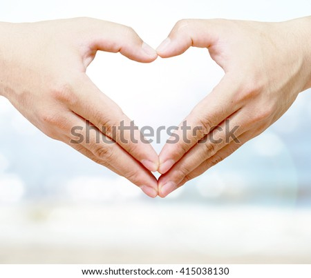 Heart-shaped hand with a marine background bokeh blur. this is sea and sky and sum and Beach blur bokeh background. Sea and Sea Dream Master - stock photo