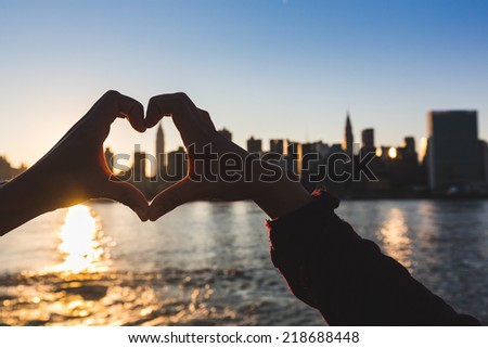 Heart Shaped Hands at Sunset, New York Skyline on Background - stock photo