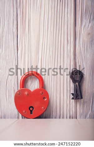 Heart shaped lock and key over light vintage wooden background - stock photo