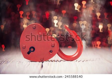 Heart shaped lock over defocused light shaped like keys - stock photo