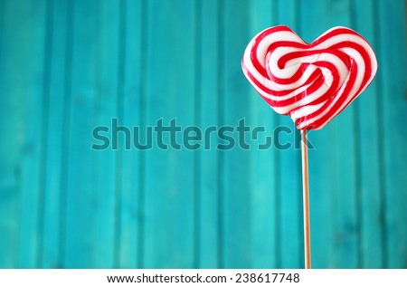 Heart shaped lollipop for Valentine's Day with turquoise copy space background - stock photo