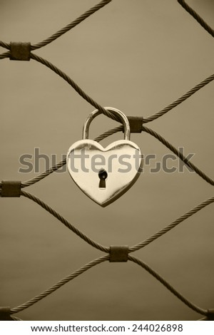 Heart shaped love padlock in Paris. Valentine's day background. Aged photo. Sepia. - stock photo