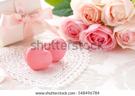 Heart shaped macaroons with Bouquet of pink roses and gift on the table