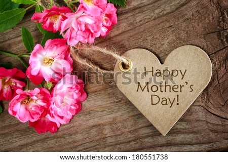 Heart shaped mothers day card with roses on wood background - stock photo
