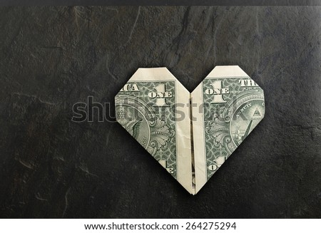 Heart shaped origami dollar on black textured background                                - stock photo