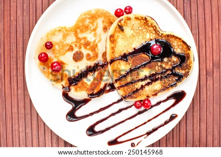 Heart shaped pancakes with chocolate sauce and red cranberries on white porcelain plate. Celebration dessert. Indoors closeup. - stock photo