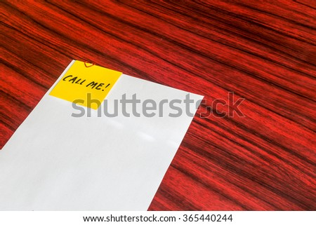 Heart shaped paper clip attached to a sheet of paper with a yellow sticky note. The word Call me written on the note. - stock photo