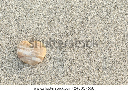 Heart shaped pebble on the sand beach - stock photo