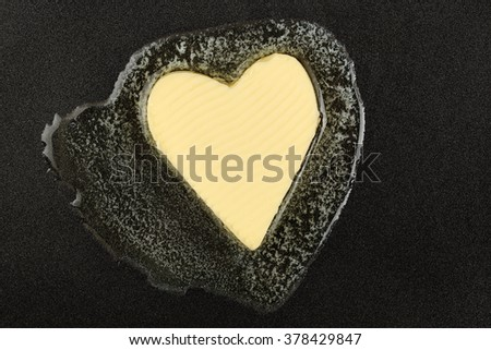 heart-shaped piece of butter melting on black pan